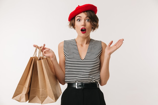 Portrait of elegant woman in striped shirt and red beret holding shopping bags, isolated over white