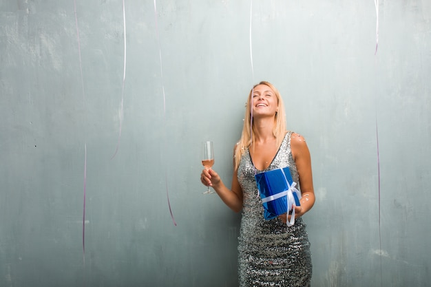 Portrait of elegant young blonde woman drinking champagne and holding a gift, celebrating new year with confetti.
