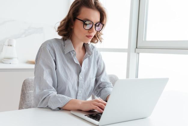 Ritratto del email mandante un sms della giovane donna elegante sul computer portatile mentre sedendosi alla tavola nella stanza leggera