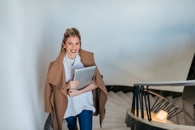 Portrait of elegant young woman walking up the stairs, holding laptop.