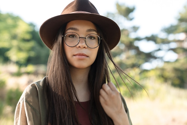 Portrait of elegant young woman with long dark hair wearing stylish hat and eyeglasses walking in green park on sunny day