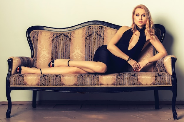 Portrait of an elegantly beautiful young woman posing on an antique couch.