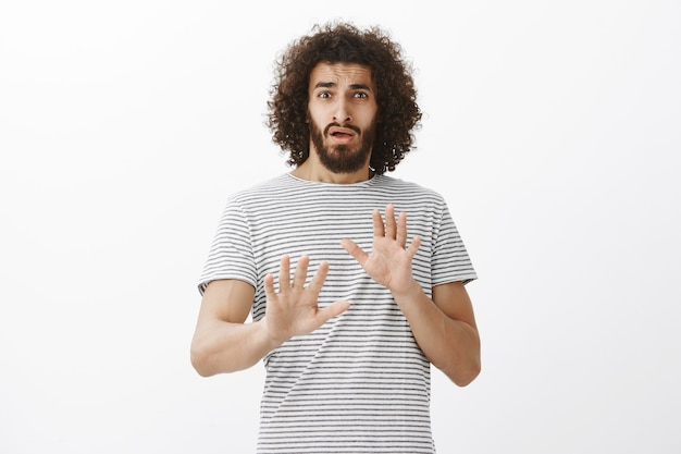 Portrait of embarrassed cute hispanic boyfriend with beard, being surprised with unexpected offer, raising palms in no or rejection gesture, trying to deny something or refuse