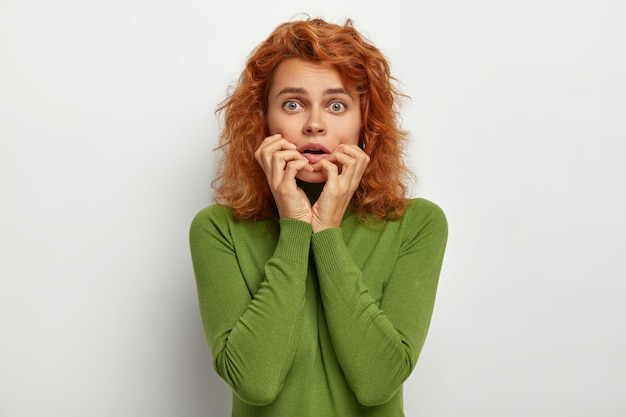Portrait of embarrassed nervous woman has scared worried expression, keeps hands near opened mouth, afraids of hearing terrible news, has natural ginger hair, dressed in green casual clothes