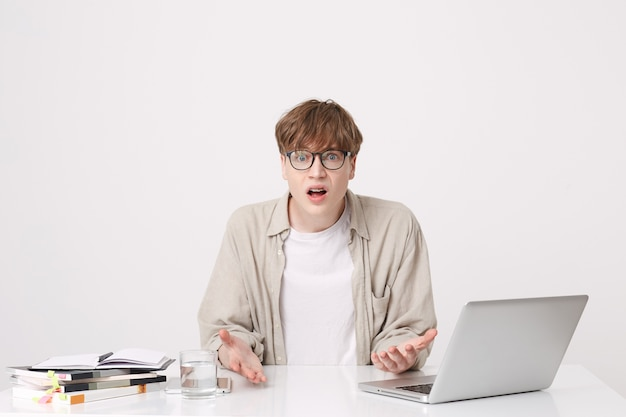 Portrait of embarrassed shocked young man student wears beige shirt and spectacles looks confused sitting at the table with laptop computer and notebooks isolated over white wall