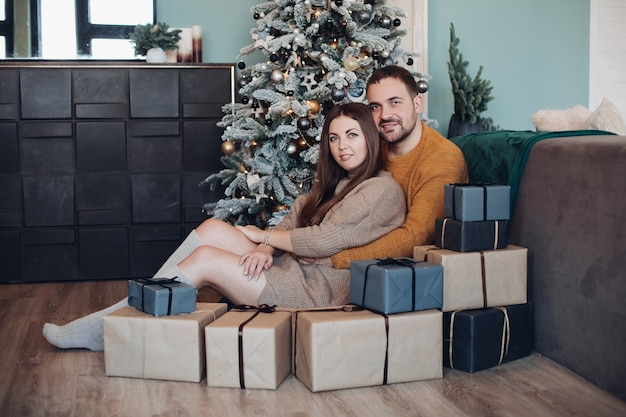 Portrait of embracing couple sitting with stack of wrapped gifts