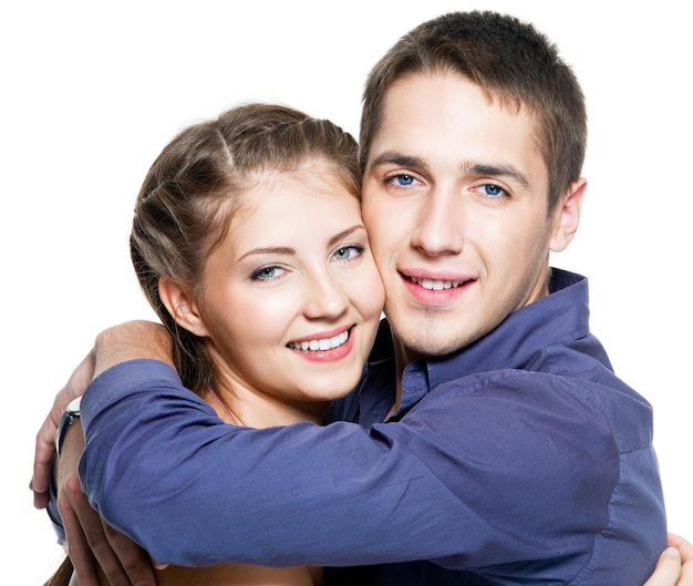 Portrait of embracing young happy beautiful couple - white wall