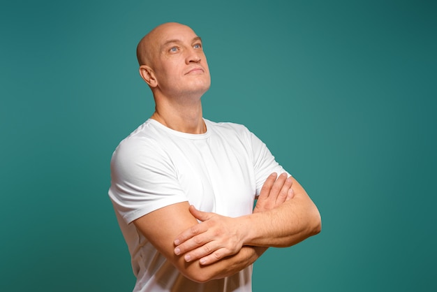 Portrait of an emotional bald man in a white t-shirt on a blue background.