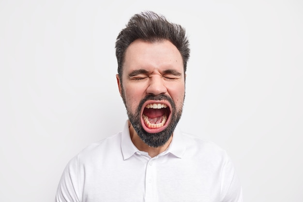Portrait of emotional bearded mad european man keeps mouth wide opened closes eyes has thick beard dressed in shirt