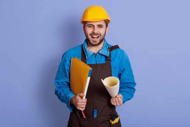 Portrait of emotional handsome builder standing isolated over blue wall in studio, holding papercase, opening mouth widely, shouting, having beard, wearing blue overall, helmet and brown apron.