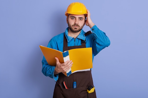 Portrait of emotional magnetic helpless young builder , holding papercase, putting one hand on helmet, having working day, being busy. people and work problems concept.