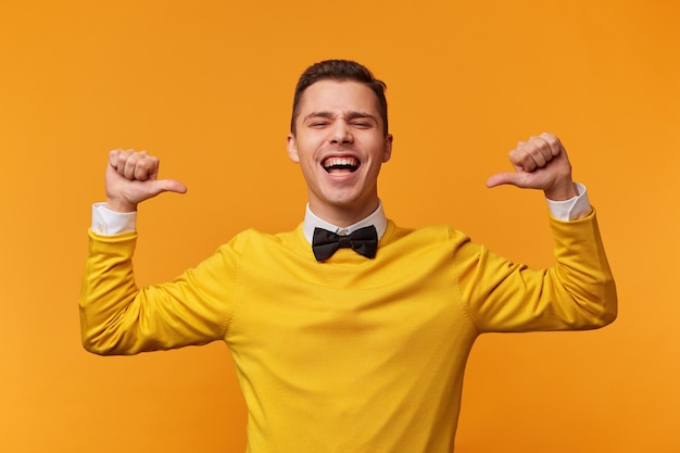 Portrait of emotional man with bow-tie isolated on yellow wall screaming with joy and victorious expression, holding hands in gesture of winner