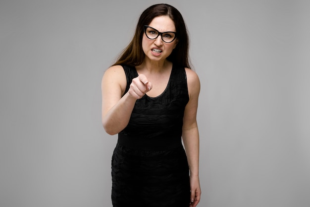 Portrait of emotional pretty confident puzzled astonished plus size model standing in studio pointed finger on camera on gray background