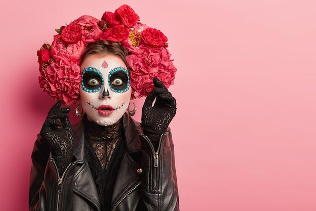 Ritratto di donna emotiva indossa trucco professionale del cranio dello zucchero, ha l'espressione del viso spaventato, alza la mano in guanti neri con orrore, si prepara per le vacanze di halloween