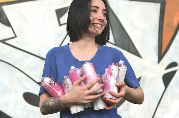 Portrait of an emotional young girl with black hair and holding sprays