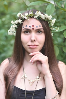 Portrait of an emotional young girl with a floral wreath on her head and shiny ornaments on her forehead.