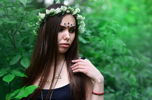 Portrait of an emotional young girl with a floral wreath on her