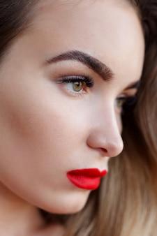 肖像画、感情、人々、美しさの概念-赤い唇を持つファッションアートスタジオの肖像画の女性。ファッショナブルな口紅。プロの化粧品。大きなセクシーな唇を持つ黒のドレスの美しさの肖像画。