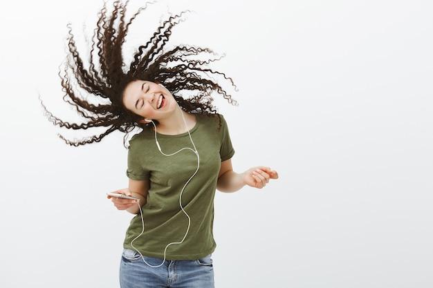 Ritratto di donna attraente spensierata iper-emotiva con i capelli ricci, cantando insieme alla musica mentre si ascoltano le canzoni in auricolari, tenendo lo smartphone e godendosi grandi pezzi