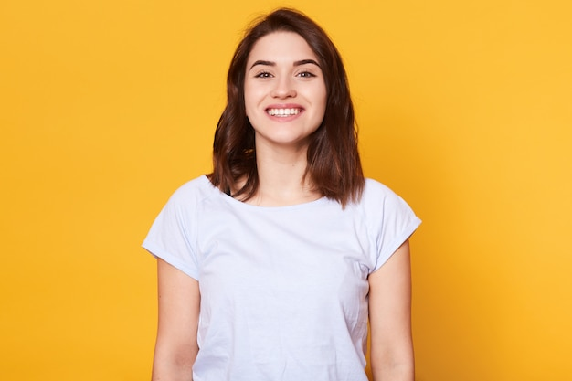Portrait of emotive good looking caucasian woman laughs while looking directly at camera