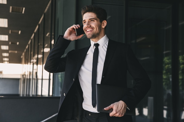 Portrait of employee man dressed in formal suit walking outside glass building, and talking on mobile phone