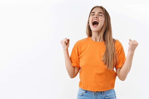 Ritratto di ragazza bionda sollevata e autorizzata, studentessa che grida sì in cielo, chiude gli occhi e sorride dalla felicità e gioisce, pompa a pugno, trionfa sulla vittoria, celebra la vittoria o il successo