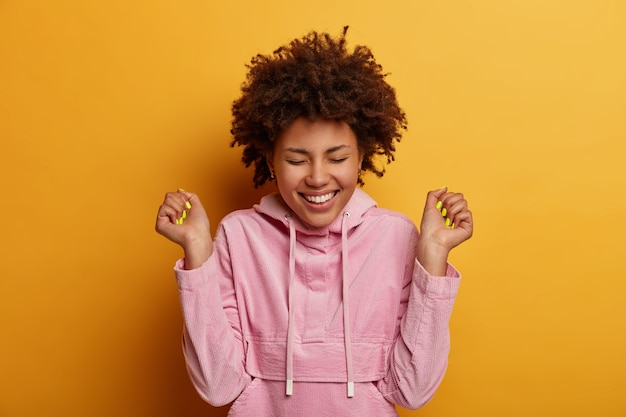Portrait of empowered relieved woman with curly hair makes fist bump smiles from happiness and rejoice triumphs over win wears pink sweatshirt celebrates victory or achievement isolated on yellow wall
