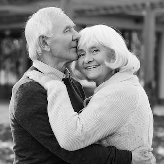 Portrait of endless love. black and white portrait of happy senior couple bonding to each other and smiling while standing outdoors and in front of their house