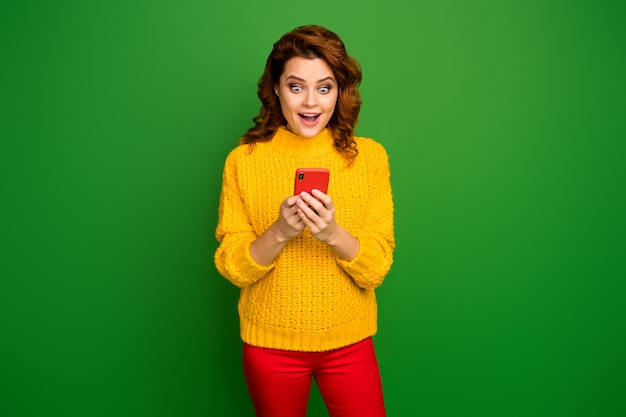Portrait of energetic crazy astonished positive cheerful woman use smartphone impressed subscribers followers scream wow omg wear stylish trendy pullover isolated bright shine color wall