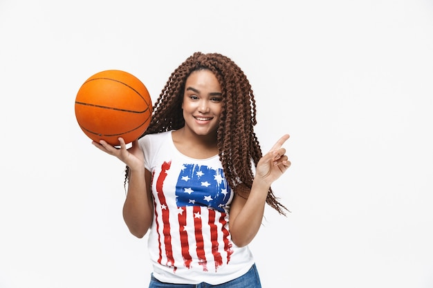 Portrait of energetic woman rejoicing and holding basketball during game while standing isolated against white wall