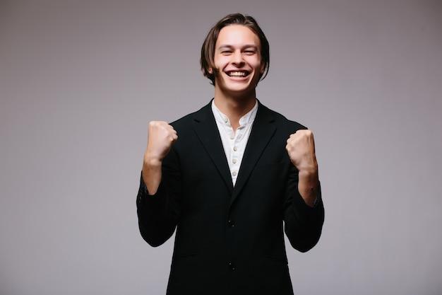 Ritratto di un energico giovane uomo d'affari che gode del successo, urlando contro il bianco - isolato