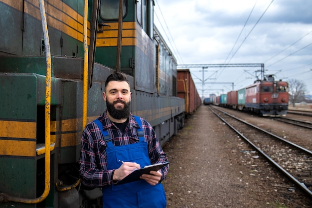 Portrait of engine train driver standing by locomotive at train station and holding departure schedule