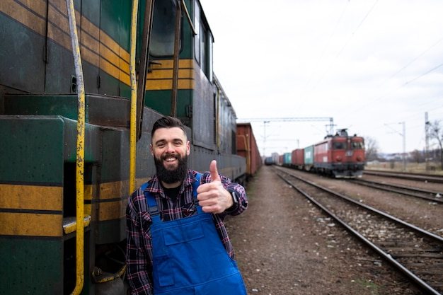 Portrait of engine train driver standing by locomotive at train station and holding thumbs up