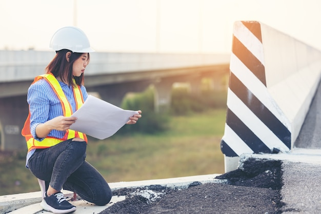 Portrait of engineer gesturing over damaged road, road workers inspecting construction
