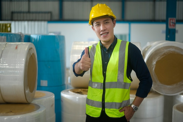 Portrait of engineer man  putting a protective helmet on  head in warehouse