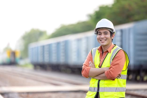 鉄道に取り組んでいる肖像画エンジニアの男。メンテナンス施設のヘルメットのチーフエンジニア、エンジニアと修理人の概念。最初に安全