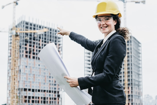 A portrait of engineer woman looking at camera. woman architect with blueprint in hand and yellow helmet with select focus. concept engineer and business work.