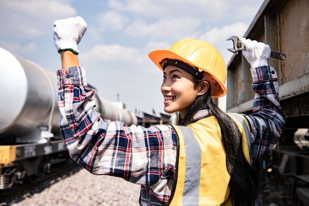 Portrait of engineers woman working on train garage site and holding wrench for repair.