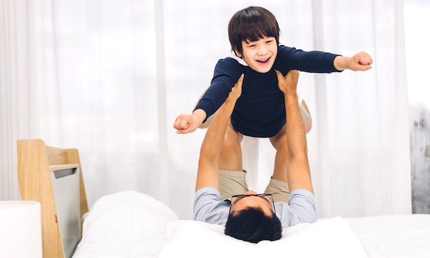 Portrait of enjoy happy love asian family father carrying little asian boy son smiling playing superhero and having fun moments good time on bed at home