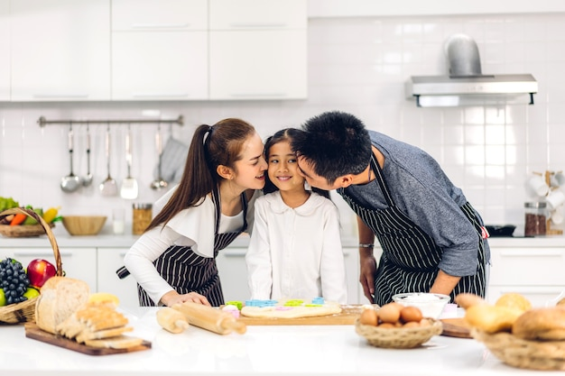 Portrait of enjoy happy love asian family father and mother with little asian girl daughter child having fun cooking together with baking cookies and cake ingredients on table in kitchen