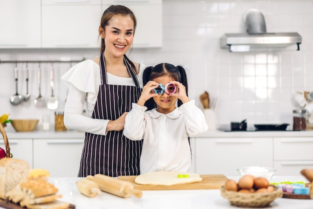 Portrait of enjoy happy love asian family mother and little asian girl daughter child having fun cooking together with baking cookies and cake ingredients on table in kitchen