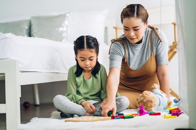 Portrait of enjoy happy love asian family mother and little asian girl smiling playing with toy build wooden blocks board game in moments good time at home