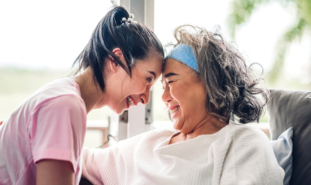 Portrait of enjoy happy love asian family senior mature mother and young daughter smiling laughing embracing and having fun together in moments good time at home