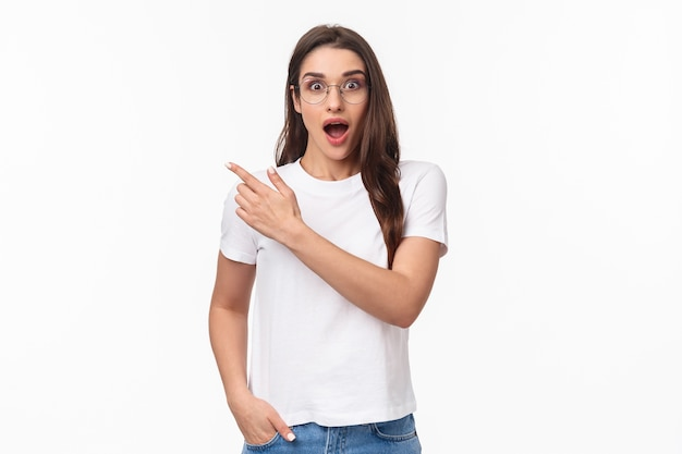 Portrait of enthusiastic, amazed and impressed young attractive girl in glasses talking