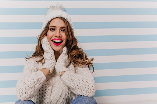 Portrait of enthusiastic, emotional lady in comfortable soft warm clothes and winter accessories seating on floor against blue-white wall