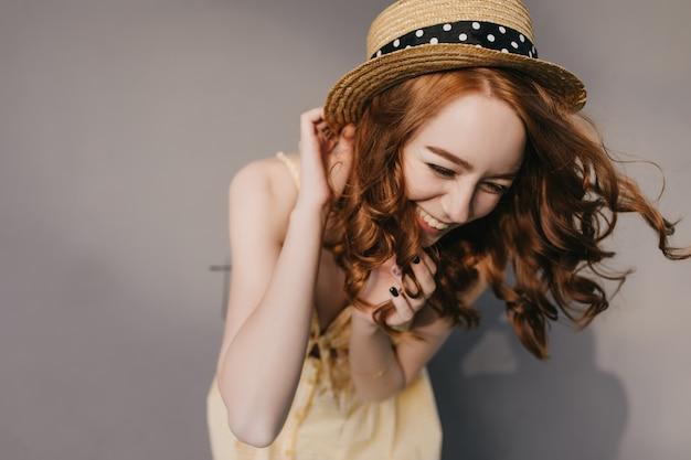 Ritratto di modello femminile entusiasta con riccioli rossi lucidi. foto di ridere ragazza caucasica divertendosi sul muro grigio.