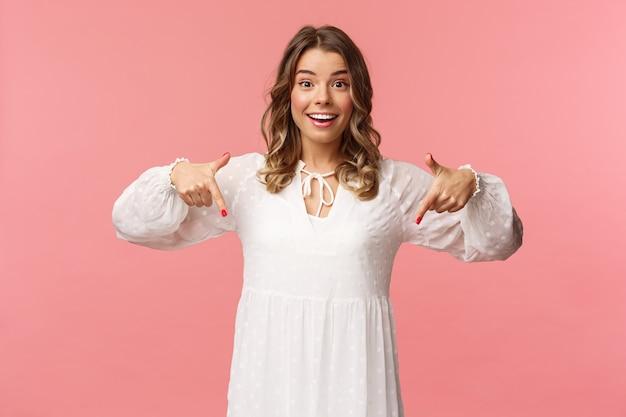 Ritratto di giovane donna bionda ottimista entusiasta che punta le dita verso il basso per invitarti a controllare il prodotto, mostrando il fondo, allegro, concetto di primavera, muro rosa.