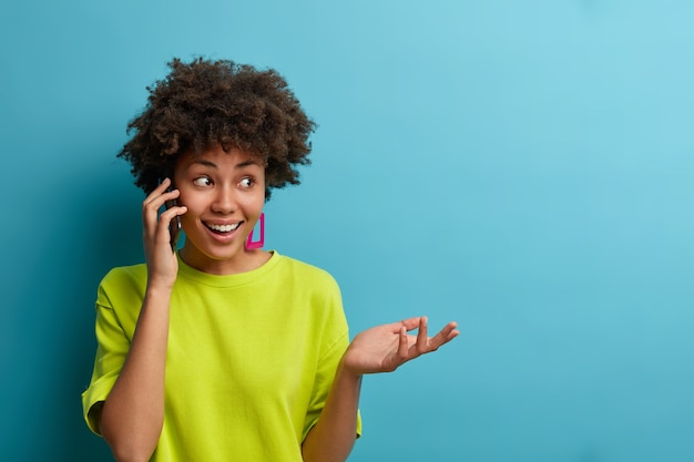 Il ritratto della donna afroamericana allegra etnica trascorre il tempo libero a casa spettegolando, tiene lo smartphone vicino all'orecchio, solleva la palma, vestito con una maglietta casual, isolato sul muro blu, uno spazio vuoto