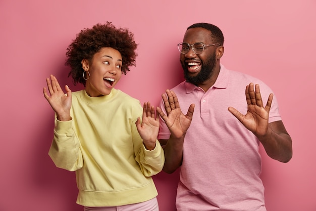 Portrait of ethnic woman and man raise palms, feel upbeat, dance and move actively on disco party, dressed casually, look with broad smiles at each other, isolated over pink background.