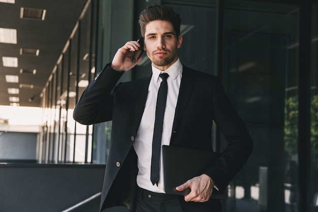 Portrait of european businessman dressed in formal suit standing outside glass building, and talking on mobile phone